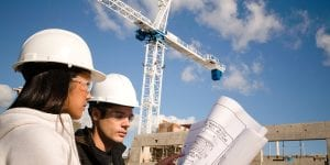 A female and male wearing white hard hats look at blueprints in front of a crane.
