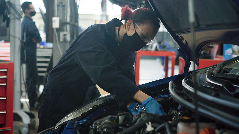 BCIT student wearing mask working under the hood of a car