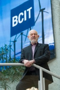 Man standing in front of large BCIT banner