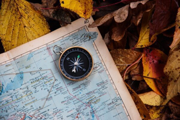 Compass and map on autumn leaves.